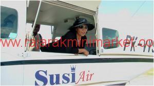 Ibu Menteri, Susi Pudjiastuti, berpose dari balik jendela pesawatnya.